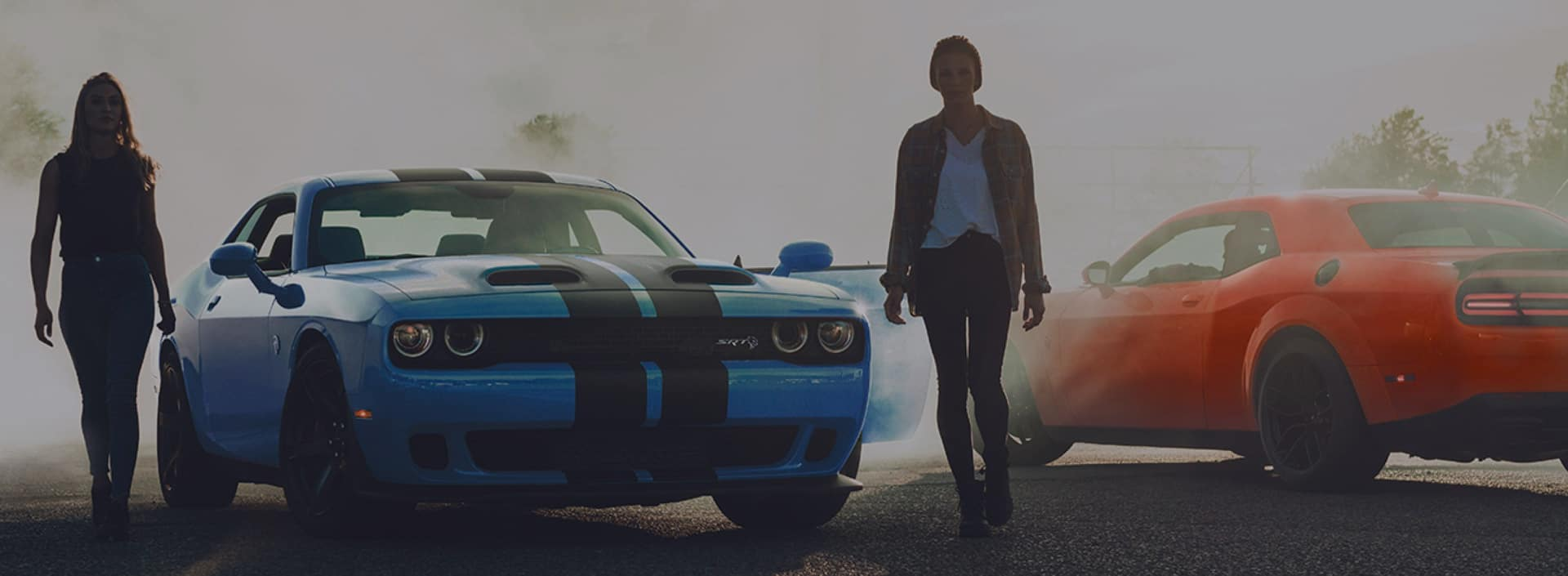 Two girls walking away from Dodge coupes