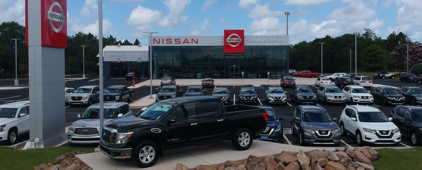 Exterior of dealership with Nissan vehicles in lot