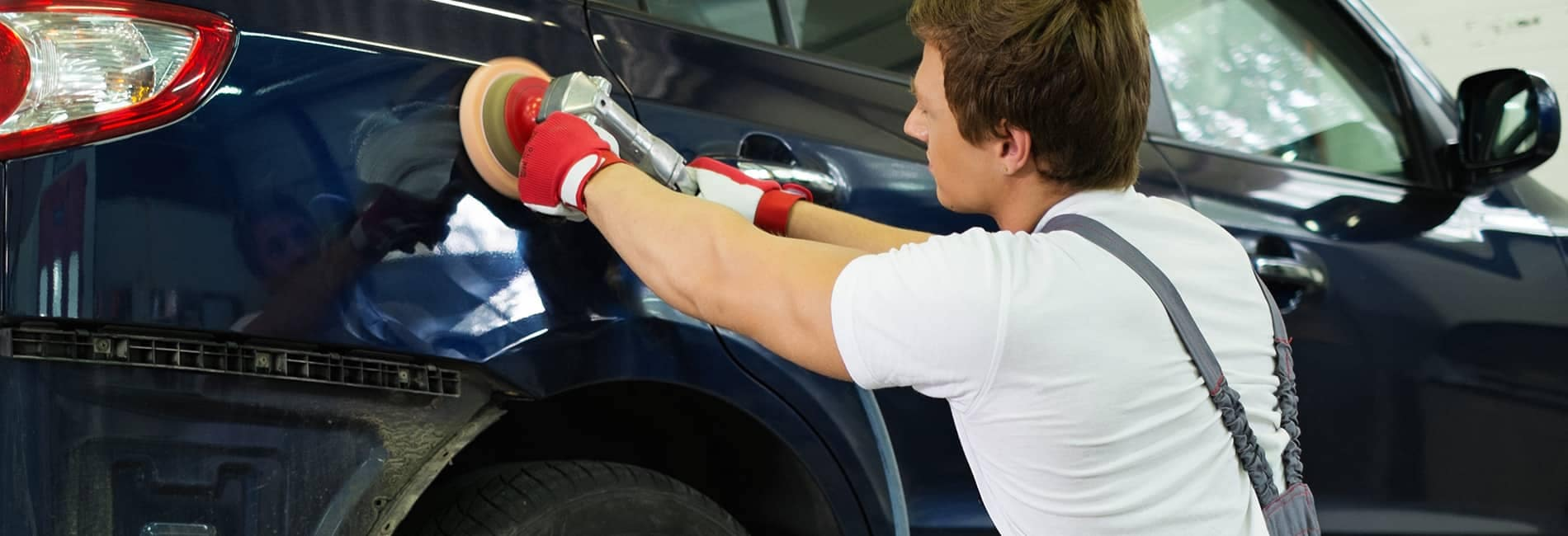 Body Shop Worker Buffing Blue Vehicle