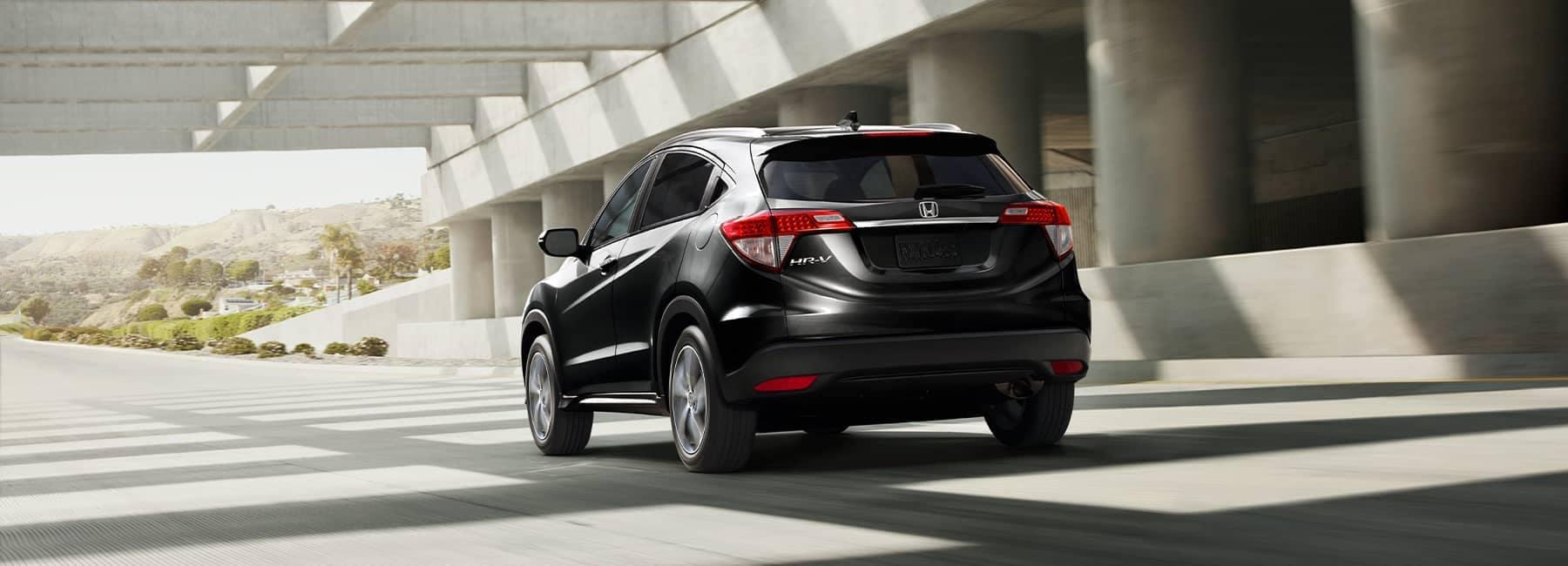 2021 Black Honda HR-V driving under a highway overpass