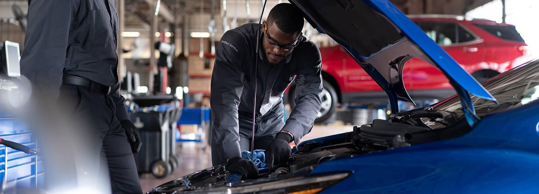 Certified technician examines under car hood
