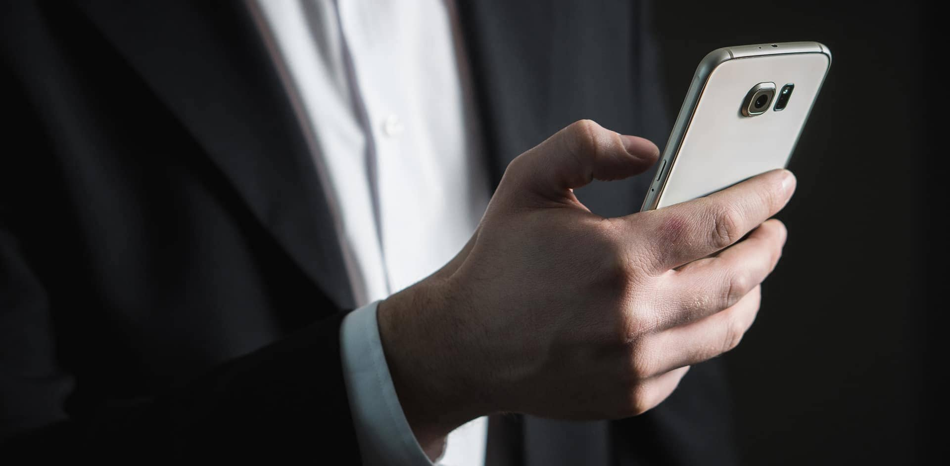 Man in Suit Holding Smartphone