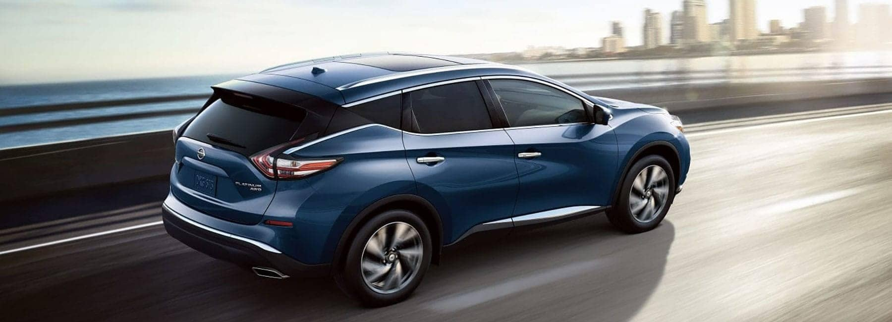 2018 Murano drives on highway alongside bay