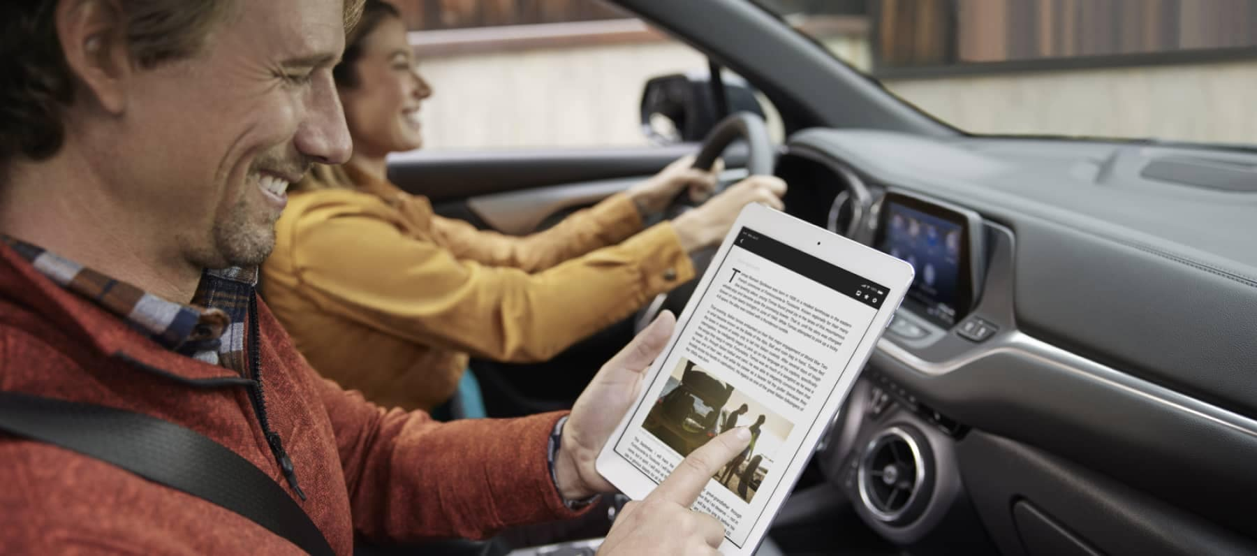 man is smiling while looking at a tablet in the passenger seat of car