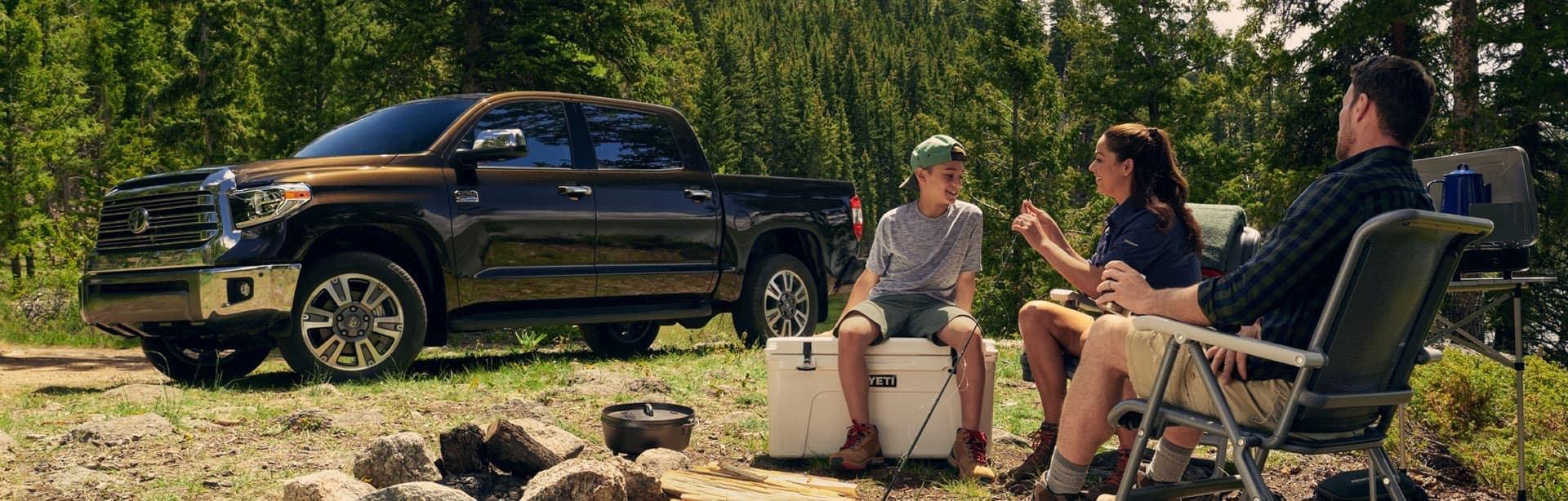 Shepard Toyota Welcome slider - men sitting around a camp fire next to a Toyota truck