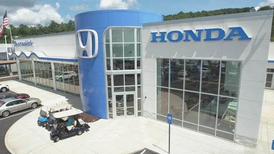 An exterior shot of a Honda dealership in the daytime.