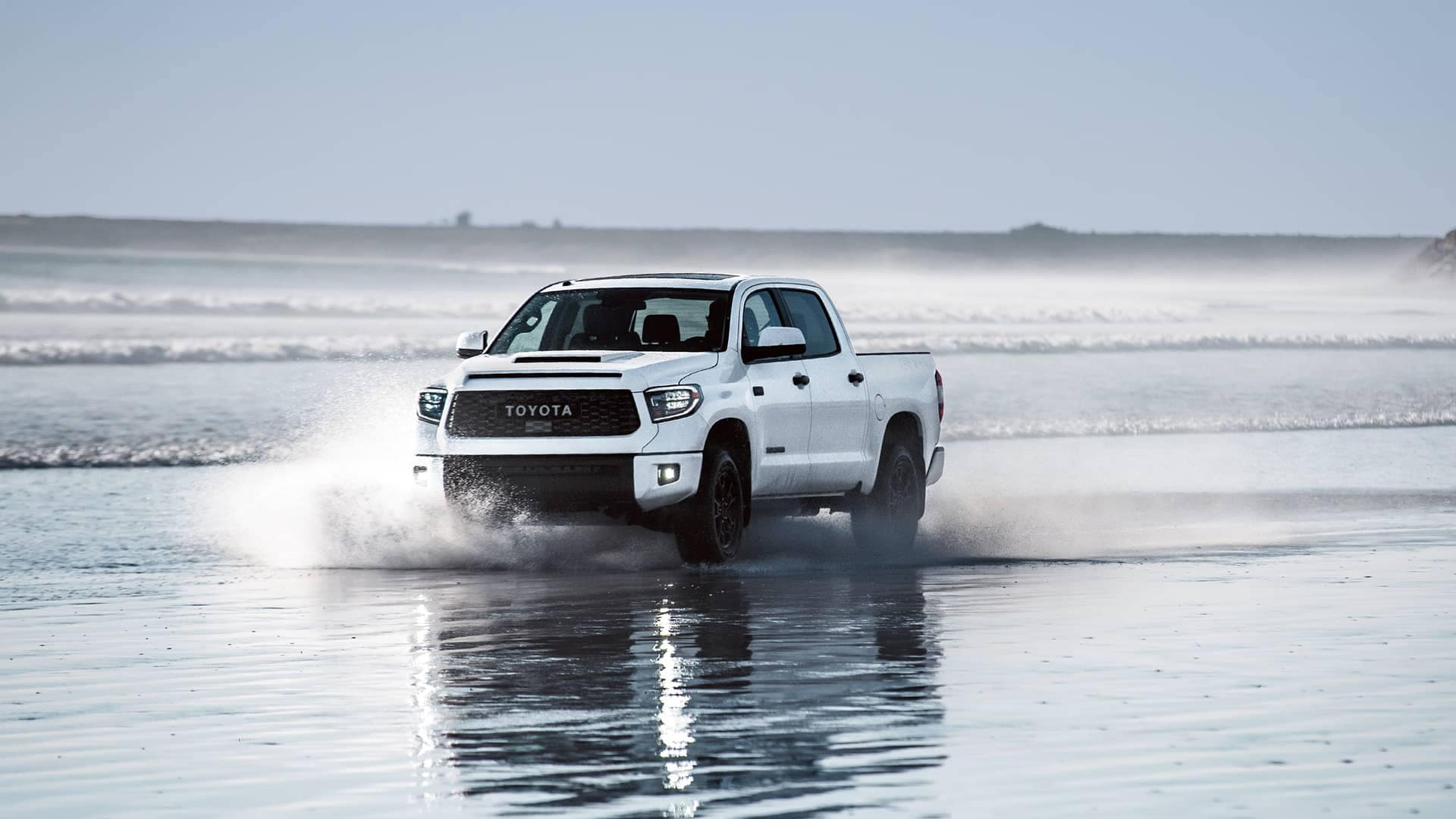 Truck driving through water on beach