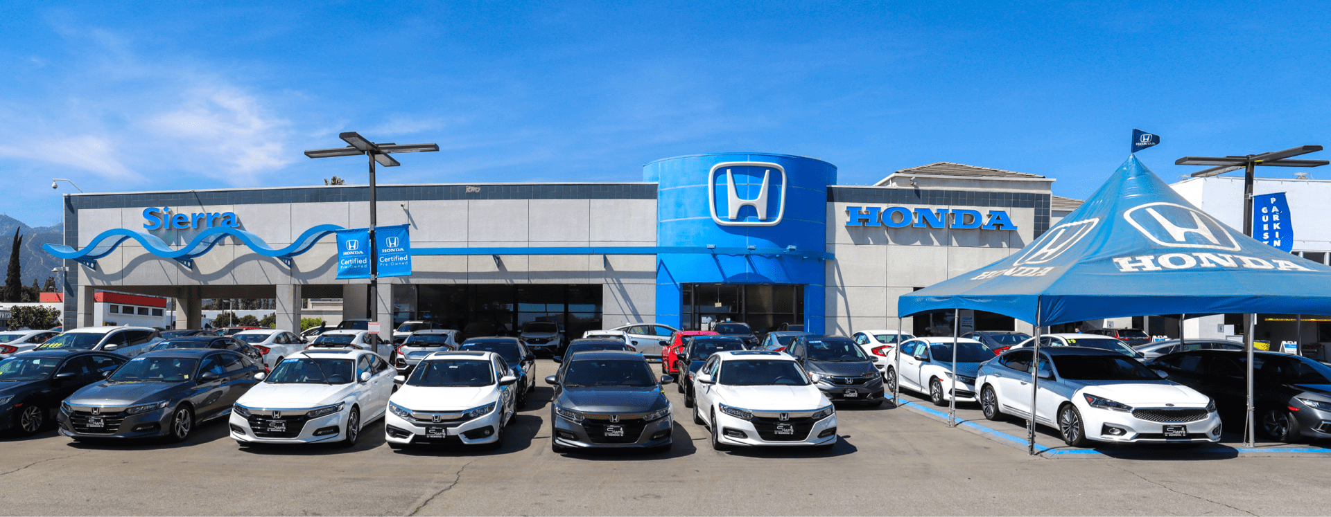 An exterior shot of a Honda dealership during the day.