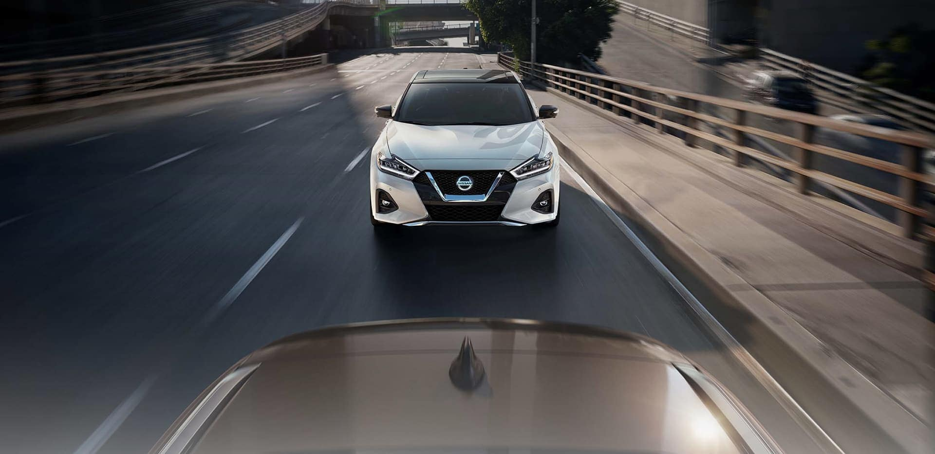 Front view of Nissan driving down street
