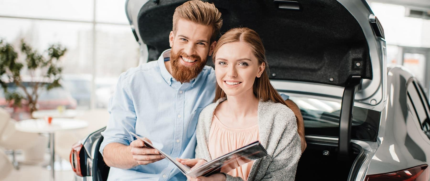 Man and woman smiling while reading vehicle booklet