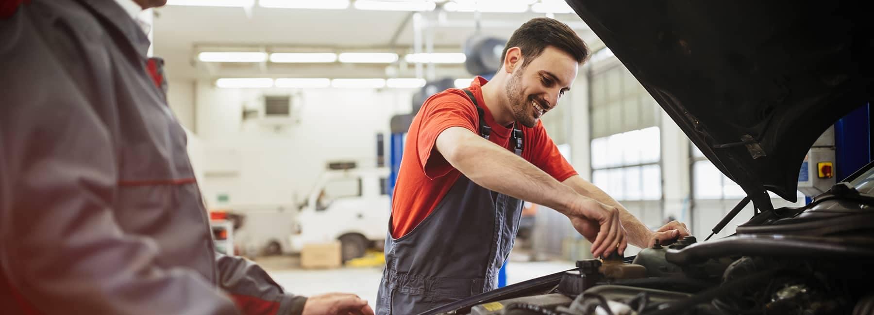 Mechanic Screwing Cap on in Car Engine