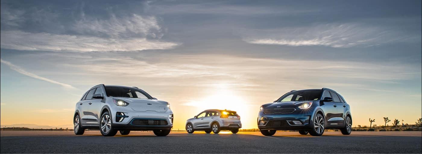 three Kia's parked durning a sun set