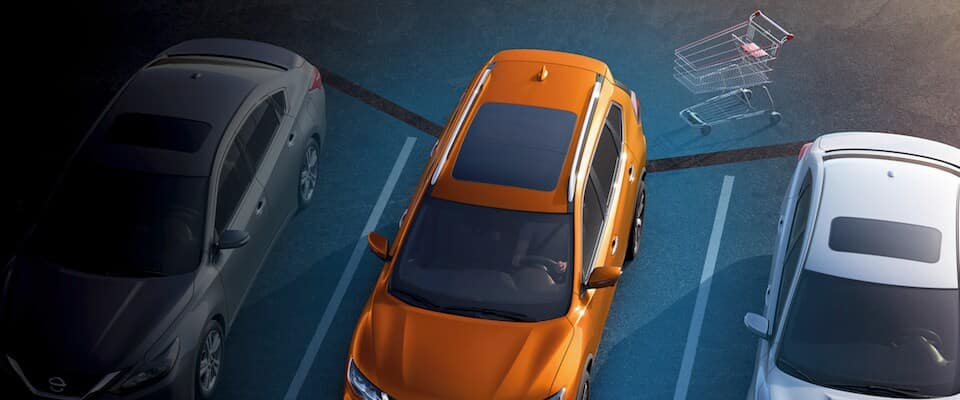 And orange Nissan Rogue using a tech feature to sense a shopping cart behind it