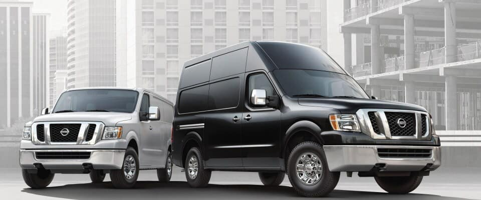 A grey and black Nissan NV Cargo and Passenger Van parked next to each other