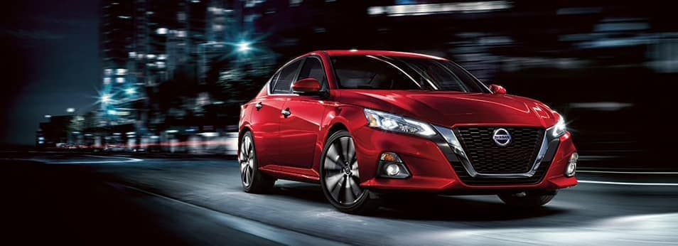A red Nissan Altima driving through the night