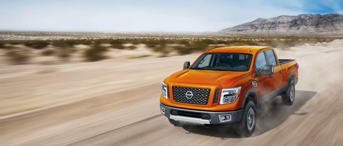 An orange 2019 Nissan Titan XD driving down a dusty road.