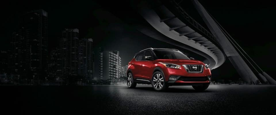A red 2018 Nissan Kicks parked under a bridge in the bright part of a dark city