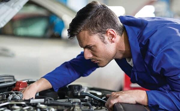 A service mechanic repairing an engine.
