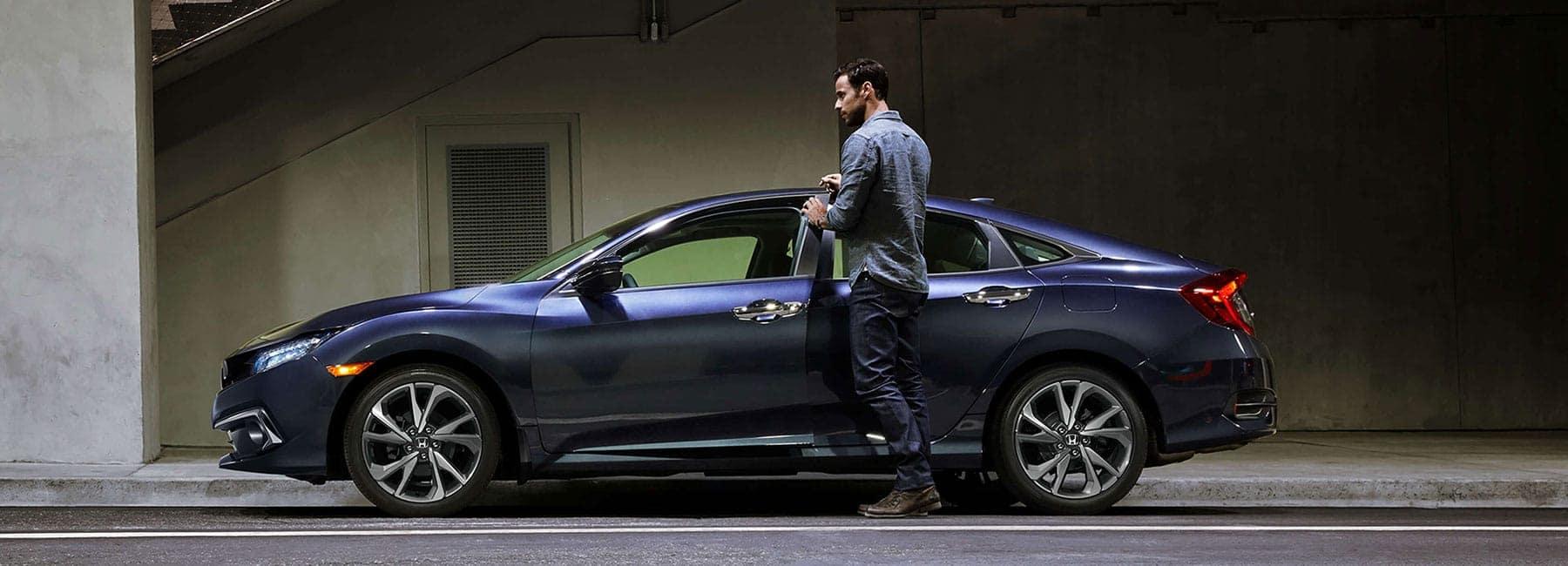 man opens driver door of Honda Civic sedan