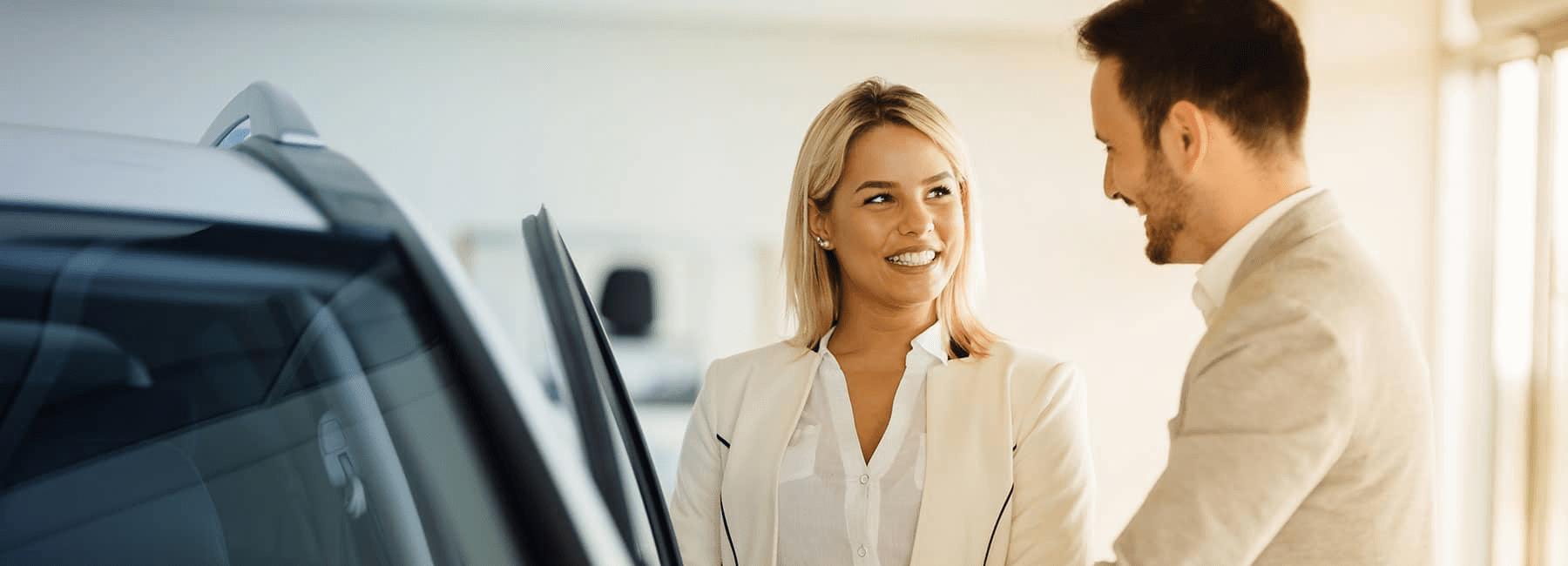 car salesman shows happy woman car in showroom