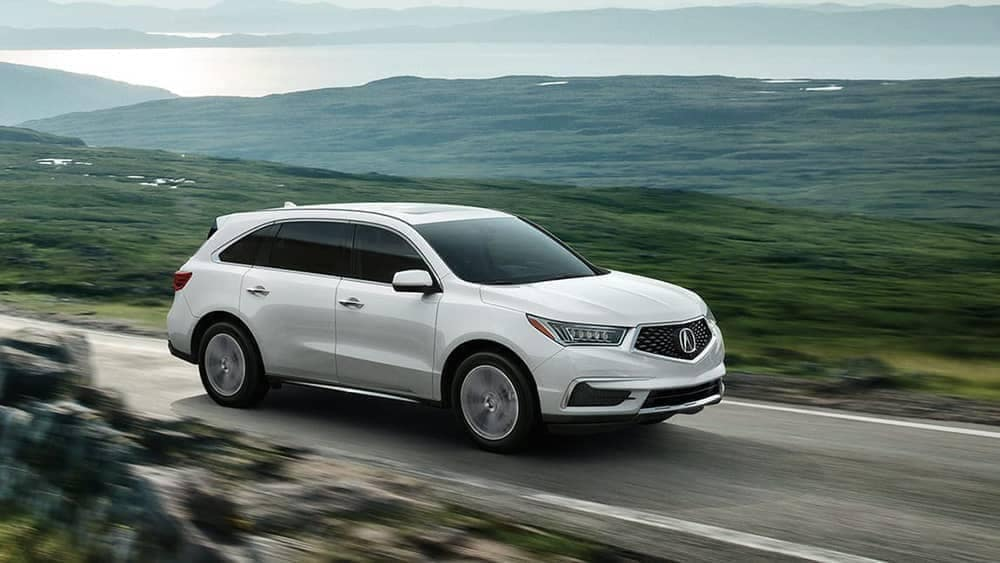2020-Acura MDX driving on a lonely road by green foothills
