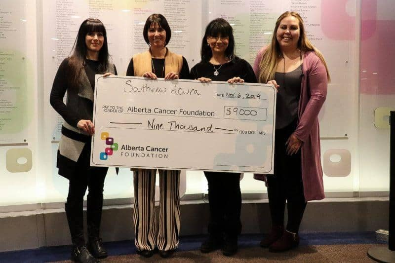 Alberta Cancer Foundation holding a check