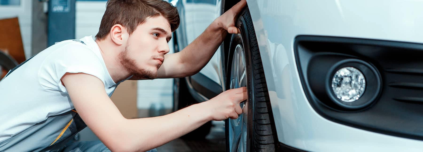 technician inspects car brakes