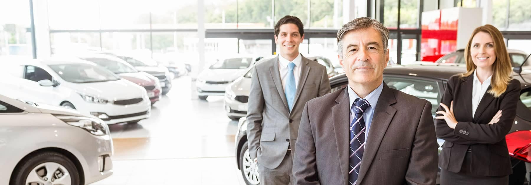 Three Dealership Salesman Standing in Showroom