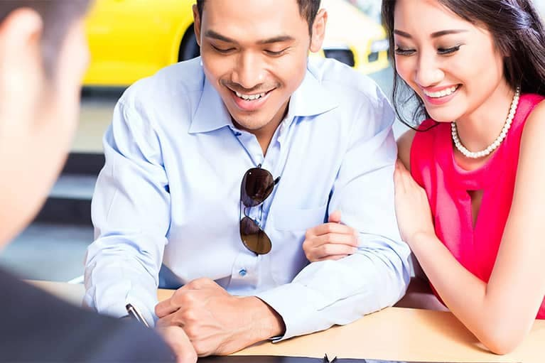Young Couple Signing Financial Documents at Dealership