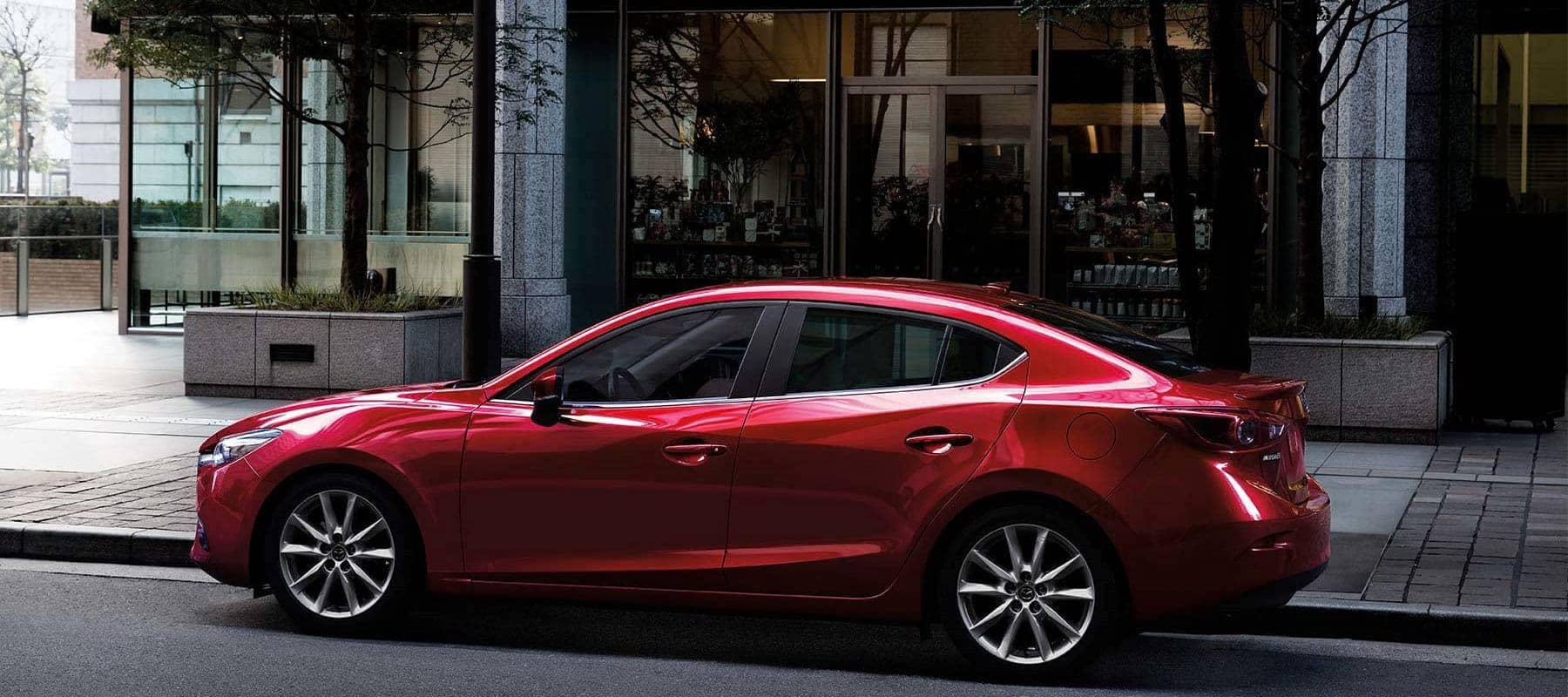 2018 Mazda3 sedan parked on city street with restaurant behind