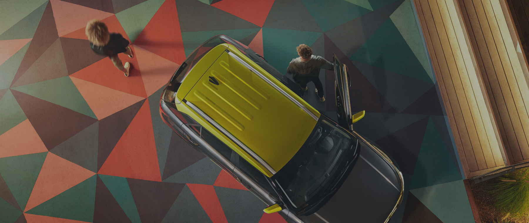 Top down of green SUV, 2 people walking away on a triangle patterned floor