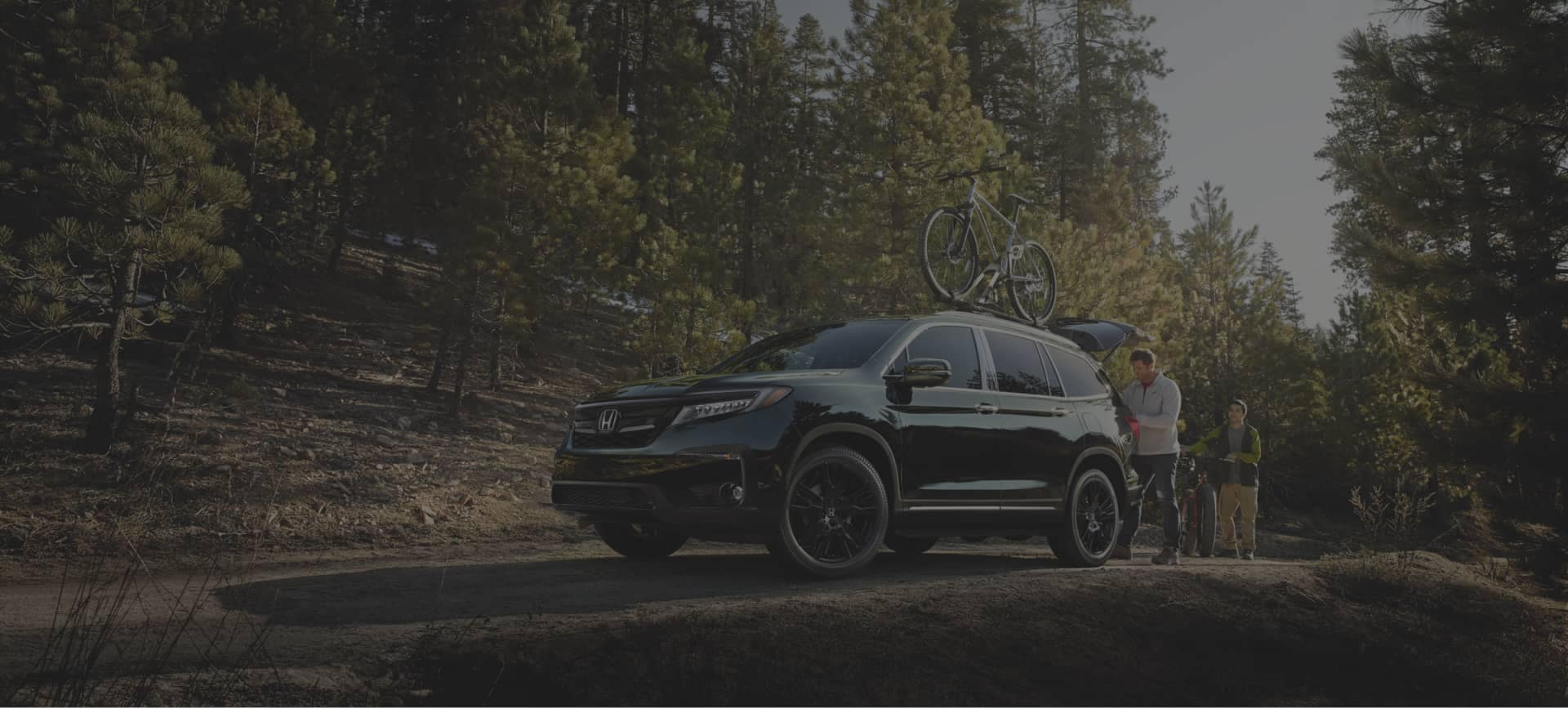two men loading trunk of Honda SUV with bike on top on a dirt path
