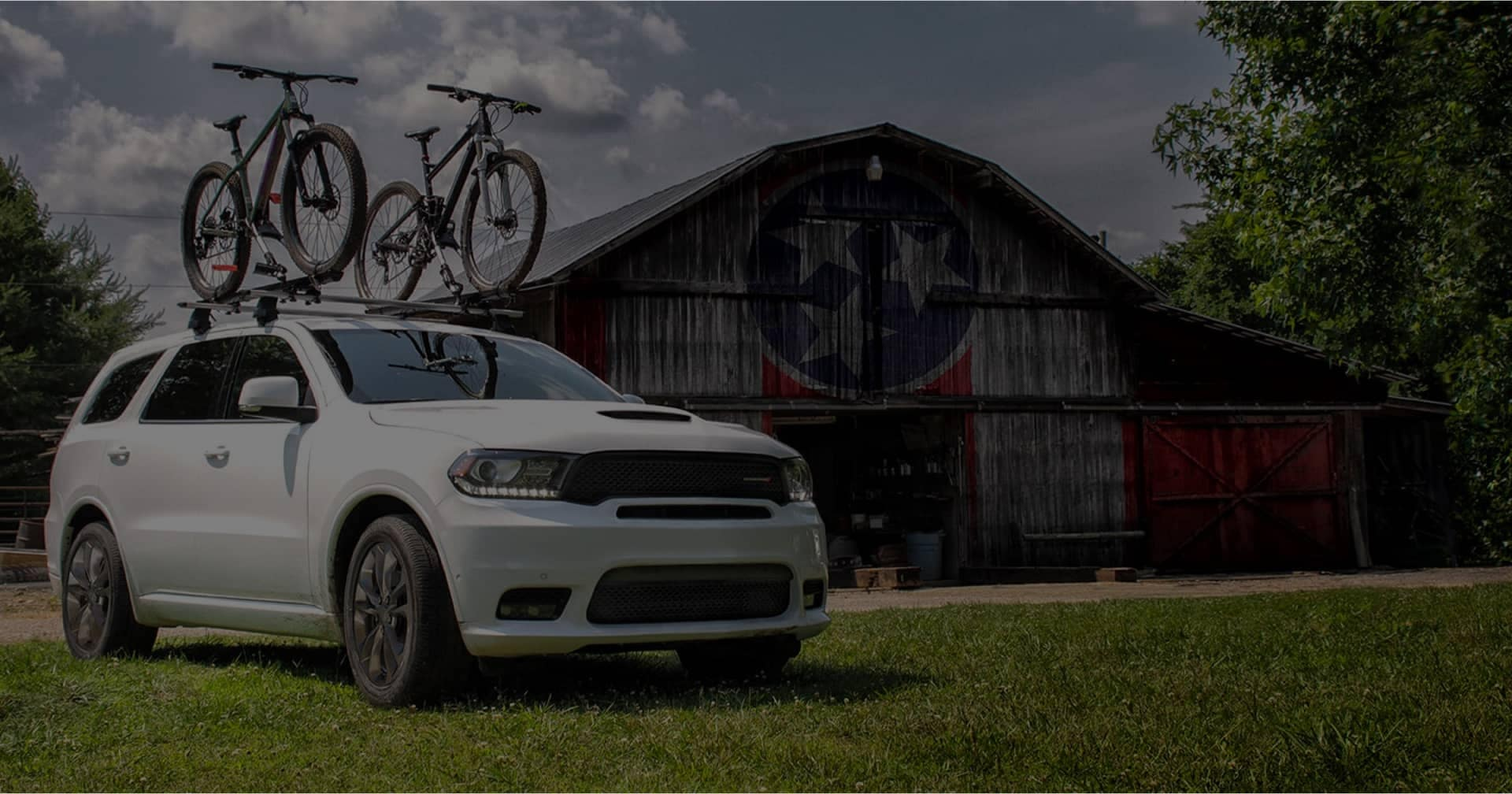 dodge suv with two bikes on top parked a lawn with a barn garage behind