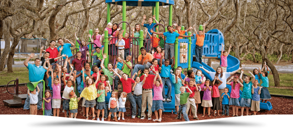 picture of dozens of children on a playground waving