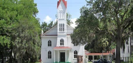 picture of a white church and tall steeple surrounded by tall trees