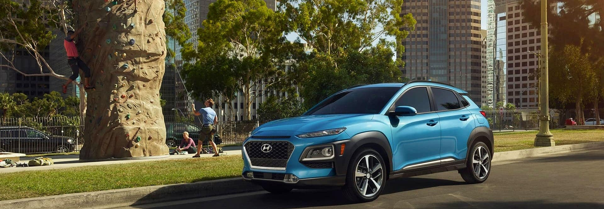 A blue Hyundai SUV parked on the street next to a rock climbing wall