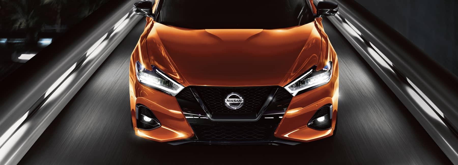 Front angle shot of a 2021 orange Nissan Maxima at night