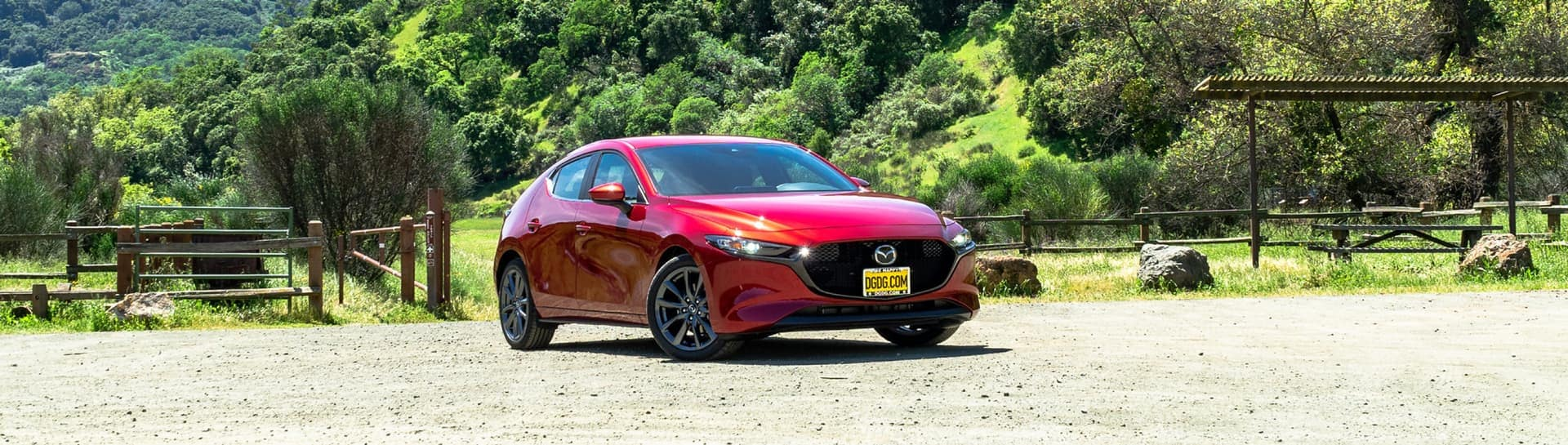 Red Mazda sedan sitting on a gravel road