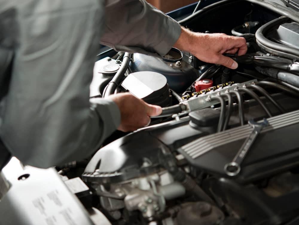 A shot of a service technician's hand, doing an oil change.