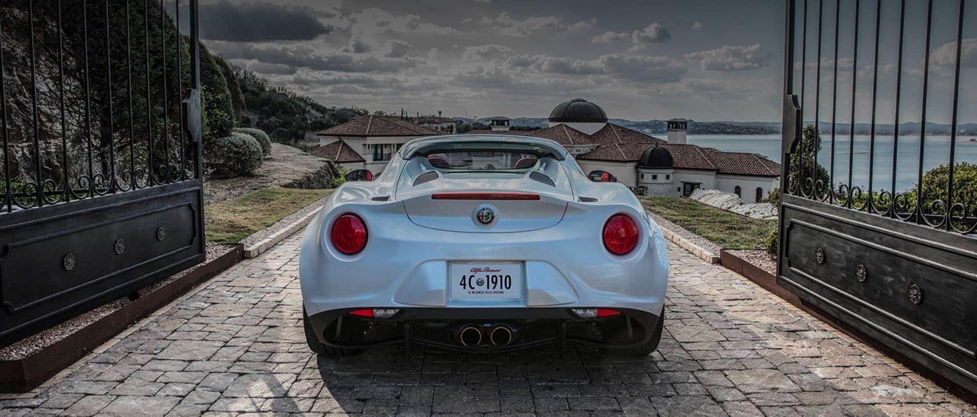 White Alfa Romeo driving out the gates into a seaside neighborhood