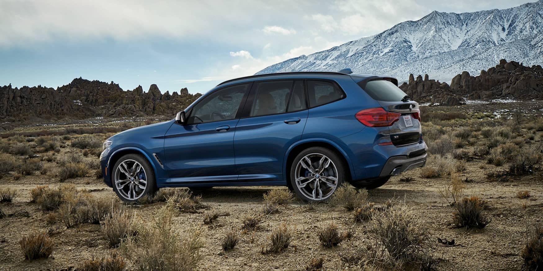 Blue 2020 BMW x3 driving on dirt road