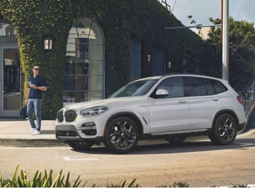 White 2020 BMW X3parked on side of road with man looking at it