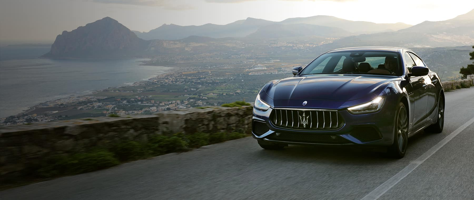 Maserati driving down a curving road in the mountains