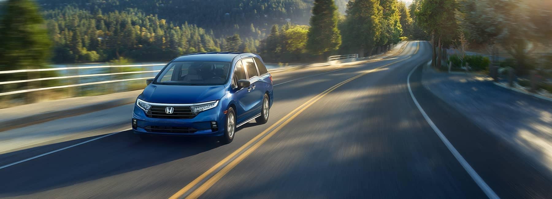 2021 Sapphire Blue Honda Odyssey driving along a mountain road