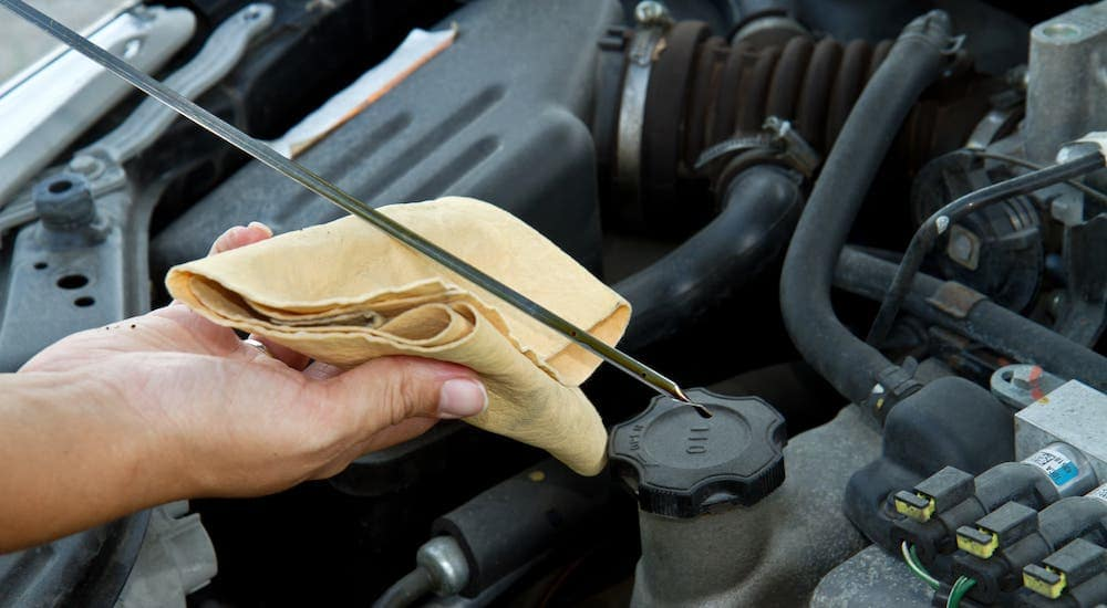 A closeup shows a hand using a rag to check the oil level on a dipstick.