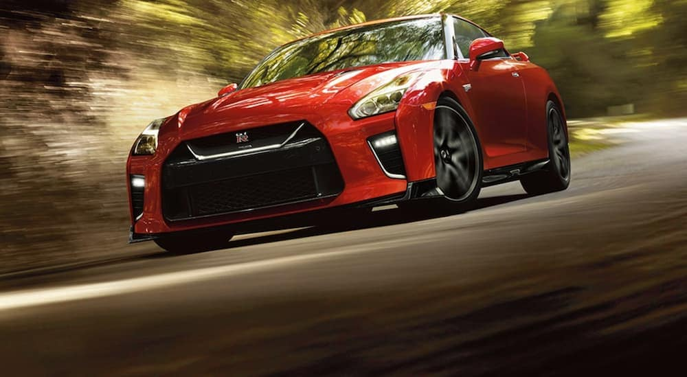 A red 2021 Nissan GT-R is driving on a track past blurred trees.