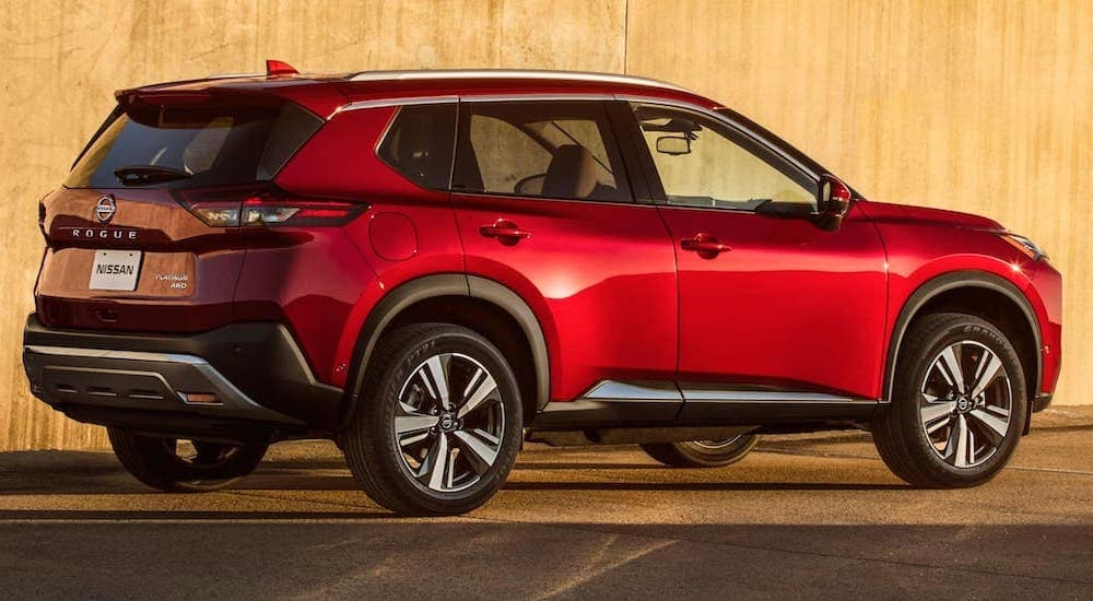 A red 2021 Nissan Rogue is shown from the side parked in front of a concrete wall at a Nissan dealer.