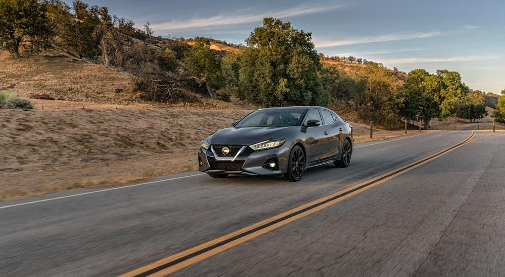 A gray 2020 Nissan Maxima from a Nissan dealer near you is driving on an empty highway past hills.