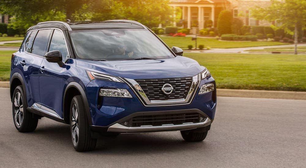 A dark blue 2021 Nissan Rogue is parked on a suburban street.
