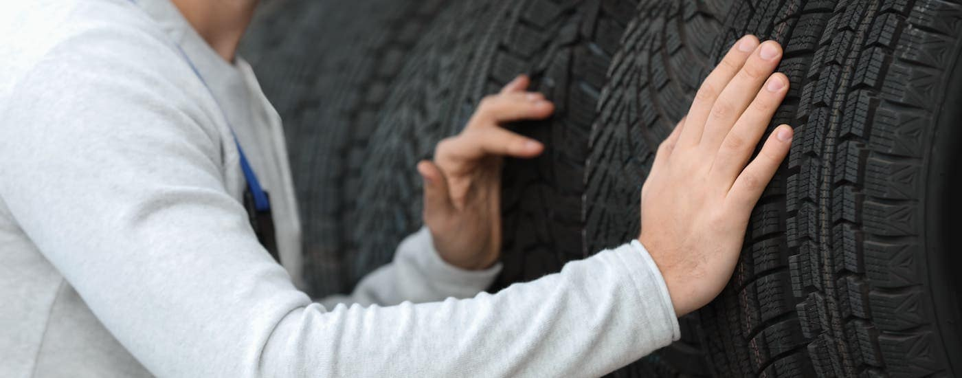 A closeup shows hands inspecting the treads on a row of tires.